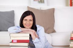 Smiling woman with a pile of books Stock Photos