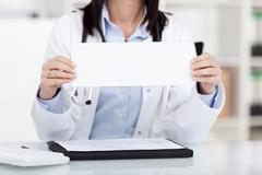 female doctor holding a blank sign - stock photo