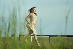 delicate lady running on the meadow - stock photo