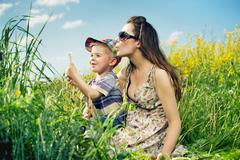 family having a lot of fun with dandelions - stock photo
