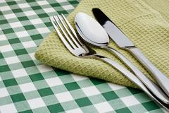 Stock Photo of flatware on green gingham table cloth