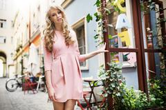 tall and pretty young model walking in old town - stock photo