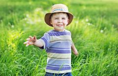 Portrait of a cute small boy playing  on the meadow Stock Photos