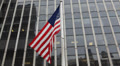 American Flag Flying Front of Steel and Glass Corporate Office Building Facade Footage