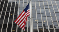 American Flag Flying Front of Steel and Glass Corporate Office Building Facade Stock Footage