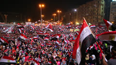 Protestors wave flags and fireworks go off at a nighttime rally in Cairo, Egypt. Stock Footage