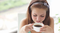 Cute girl enjoying coffee and smiling at camera - stock footage