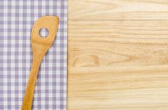 Wooden spoon on a purple checkered table cloth on a wooden background Stock Photos
