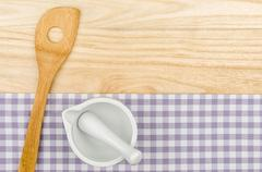 wooden spoon and mortar on a purple checkered table cloth on a wooden backgro - stock photo