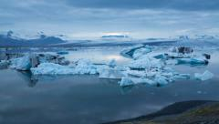 blue icebergs floating under midnight sun - stock footage
