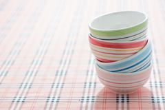 Stack of colorful bowls on fabric background Stock Photos