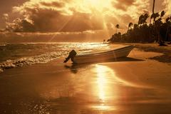 Beach with palm trees and boat at sunset time Stock Photos
