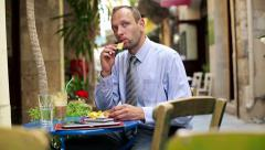 Young businessman eating chips and drinking frappe in cafe HD Stock Footage