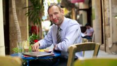 Happy businessman with laptop in cafe HD - stock footage