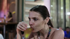 Beautiful woman drinking cocktail in outdoor bar, steadicam shot HD - stock footage