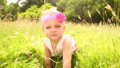 Cute baby girl smiling while crawling over grass Stock Footage
