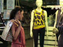 Woman with shopping bag looking at shop window, steadicam shot NTSC Stock Footage