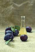 plum brandy or schnapps and tasty plum fruit. - stock photo