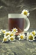 Stock Photo of cup of tea and chamomile flowers