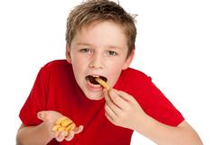 Handsome young boy eating fries Stock Photos