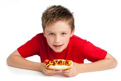 handsome young boy eating a hotdog - stock photo