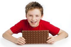 boy eating huge chocolate bar - stock photo