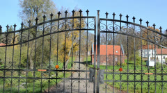 Retro steel metal gates autumn park old architecture buildings Stock Footage