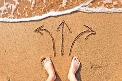 men's bare feet in the sand and arrows - stock photo