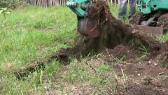 A Mini digger excavating a trench on grassy land unearths metal Stock Footage