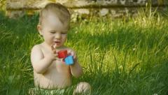 Stock Video Footage of HD1080p25 Little baby playing with color blocks on green meadow.