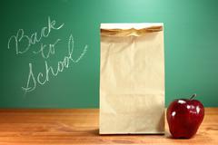 school lunch sack sitting on teacher desk - stock photo