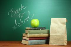 books, apple and lunch on teacher desk - stock photo