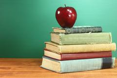 Back to school books and apple with chalkboard Stock Photos