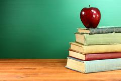 back to school books and apple with chalkboard - stock photo