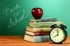 School books, apple and clock on desk at school Stock Photos
