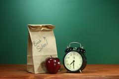 school lunch, apple and clock on desk at school - stock photo