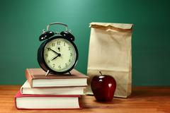 lunch, apple, books and clock on desk at school - stock photo