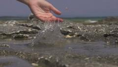 SLOW MOTION: splashing sea water with hand Stock Footage