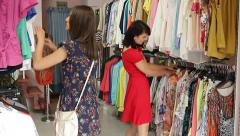 Girls run across a rack of clothes in a boutique, trying to find dresses. Stock Footage