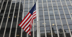 Ultra HD 4K American Flag Flying Front of Steel Glass Corporate Office Building Stock Footage