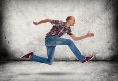 man running. gray concrete wall and floor - stock photo