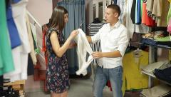Dress salesman shows to a girl customer pieces of modern suits. Stock Footage