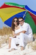 Man woman couple sunglasses multi colored beach umbrella Stock Photos