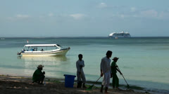 Beach cleaners, boat and cruiseship at Bali beach Stock Footage