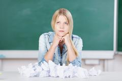 Stock Photo of student sitting in front of crumpled paper