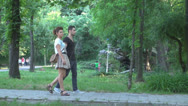 Stock Video Footage of Young couple to promenade in park,Young couple walking in park,