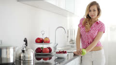 Blond girl standing in kitchen holding apple and smiling at camera Stock Footage
