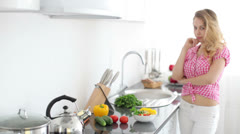 Pretty blond girl in kitchen holding bowl of salad and smiling at camera Stock Footage