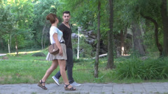 Young couple to promenade in park,Young couple walking in park, Stock Footage