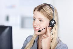 customer service executive using headset while conversing - stock photo